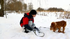 Boy playing with his dog in snow in the park in winter, English Cocker Spaniel Stock Footage