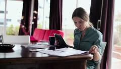 Businesswoman working with tablet computer and documents at home HD Stock Footage