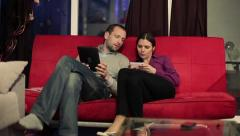 Happy couple with smartphone and tablet computer on sofa HD Stock Footage