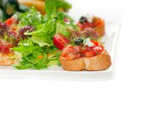 original italian fresh bruschetta served with fresh salad and vegetables on b - stock photo