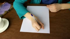 Girl writes a letter with a pen, white sheet of paper Stock Footage