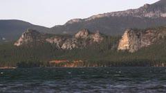 Ducks float on the lake against rocks. Stock Footage