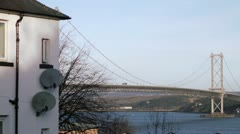 Wide panning shot of Forth Bridges with house - stock footage