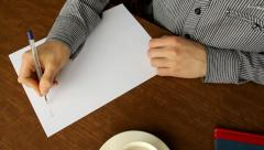 Man writes a letter on a white sheet of paper with a pen, handwriting - stock footage