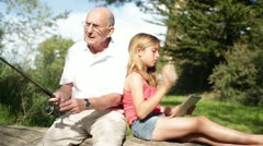 Grandfather Catches Fish with Granddaugther Stock Footage
