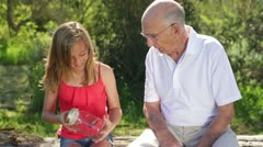 Granddaughter Shows Butterfly in Jar to Grandfather Stock Footage