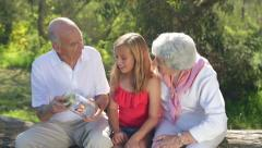Grandparents and Granddaughter Observe Butterfly in Jar Together - stock footage