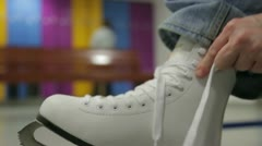 Woman takes and knotted white skates Stock Footage