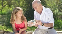 Grandfather and granddaughter look at butterfly together Stock Footage
