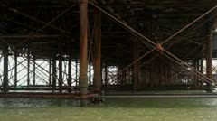 Under pier with iron bars with sea Stock Footage