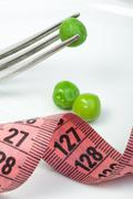 plate with peas and centimeter measure - stock photo