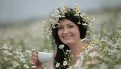 Woman with a cup in the field of daisies Stock Footage