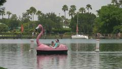 Theme Park Visitors around Lake with Flamingo Paddle Boat Stock Footage
