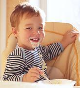 Two year old boy smiles and eating porridge. Stock Photos