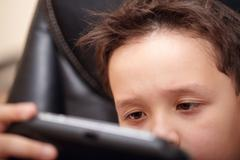 Boy tired of playing his portable game console. Stock Photos