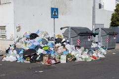 bags full of trash surrounding dumpsters, angle view - stock photo