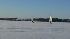 Follow two ice surfers men sail frozen lake snow extreme sport Stock Footage