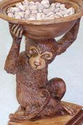 Ape simpanssi monkey tilalla kulhoon pistaasipähkinöitä Kuvituskuvat