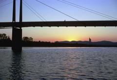 water sunset pedestrian bridge over neue donau - stock photo
