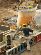 construction worker pouring concrete - stock photo