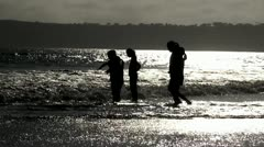 Children play with the waves on the beach. Stock Footage