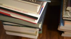 Panning across a pile of books stacked Stock Footage