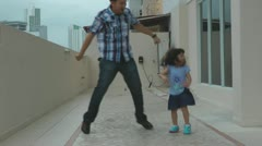 Young girl dancing with her father on the deck outdoors. Stock Footage