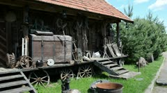 Old retro rural equipment tools chest wheels old rural log house Stock Footage