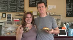Business owners at their cafe smiling holding coffee and pastries - stock footage