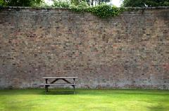 picnic table and wall - stock photo
