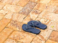 Discarded flipflops on paved deck by pool Stock Photos