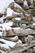 stacked wood and snow - stock photo