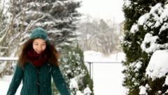 Young girl running in the garden, enjoys winter in a snowfall Stock Footage