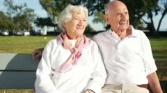 Elderly Couple Enjoying Sunny Day Together on Bench Stock Footage