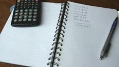Close-up of a notebook with a calculator and pen on the desk Stock Footage