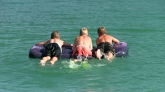 3 Boys swim with air mattress Stock Footage
