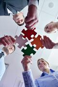 group of business people assembling jigsaw puzzle - stock photo