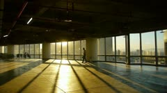 A tired man walking in business building inside platform,sunset rays light. Stock Footage