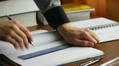 Young man studying math, writing in notebook, drawing a line with a pencil Stock Footage