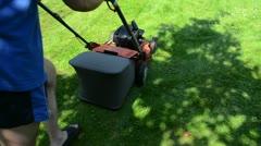 Worker man shorts flip-flop shoes push mower cut grass Stock Footage