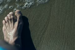 Mans foot walking on the beach, high eagle, slow motion shot at 240fps Stock Footage