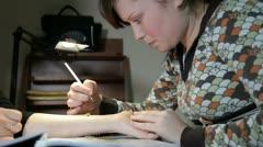 Girl making temporary tatoo on female hand Stock Footage
