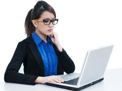 Attractive young businesswoman using laptop Stock Photos