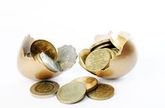 Coins in broken golden eggshell Stock Photos