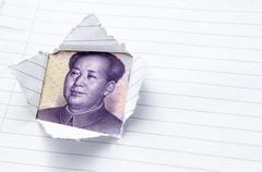 Paper page torn with window opening showing Chinese currency - stock photo