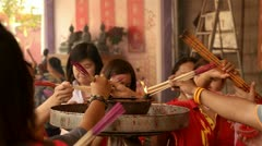 Thai People Lighting Incense Sticks at a Temple Stock Footage