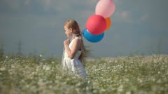 Child with balloons on meadow Stock Footage