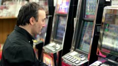 Man sitting at slot machine in casino Stock Footage