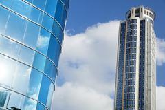 Skyscraper & part of office building Stock Photos