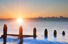 Vanha aallonmurtajat rannalla viime puolustukseen auringonnousun vastaan vuoro Kuvituskuvat